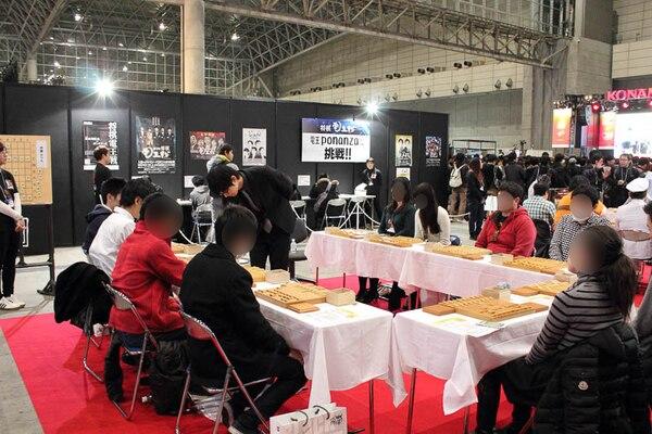 参加者10人を同時に相手する斎藤慎太郎六段。コの字に並んだテーブルの内側でスムーズに打ち進めていた