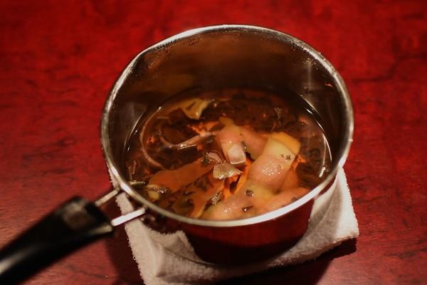 りんごの皮を使ったホットブランデーカクテルの材料を鍋で煮ているところ