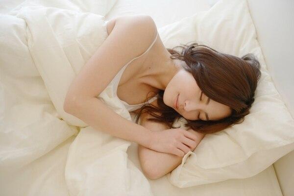 リラクゼーションミュージックを聴きながら心地よく眠る女性